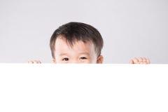 Crianças chinesas asiáticas que guardam a placa branca vazia fotografia de stock