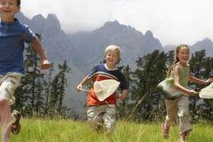 Crianças com as redes da borboleta que correm através do campo Imagem de Stock