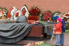 Crianças com flores e a flama eterno fotografia de stock