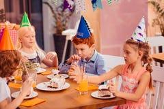 Crianças com fome que comem o bolo com grande prazer fotografia de stock royalty free