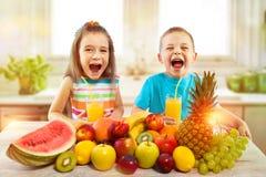 Crianças com frutos e suco fresco na cozinha, comer saudável Fotos de Stock Royalty Free