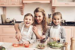 Crianças com a mãe na cozinha A mãe está ajudando crianças prepara vegetais para a salada imagem de stock