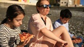 Crianças com a mãe que come a pizza na praia filme