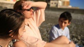 Crianças com a mãe que come a pizza na praia video estoque