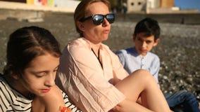 Crianças com a mãe que come a pizza na praia vídeos de arquivo