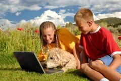 Crianças com o cão no computador Fotografia de Stock