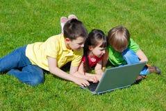 Crianças com o computador ao ar livre fotografia de stock