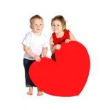 Crianças com o coração enorme feito do papel vermelho Fotos de Stock Royalty Free