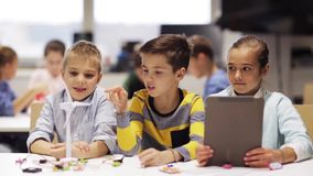 Crianças com o PC da tabuleta que programa na escola da robótica