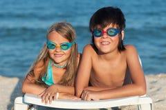 Crianças com os óculos de proteção da natação na praia imagem de stock