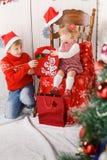Crianças com os presentes ao lado da árvore de Natal fotografia de stock royalty free