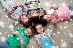 Crianças com os smartphones que encontram-se no assoalho Imagem de Stock