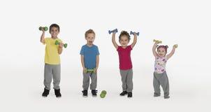 Crianças com pesos e um menino engraçado imagem de stock royalty free
