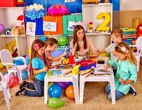 Crianças com pintura da mulher do professor no papel dentro Imagens de Stock