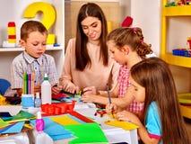 Crianças com pintura da mulher do professor no papel no jardim de infância Fotografia de Stock Royalty Free