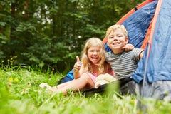 Crianças com polegares acima na barraca ao acampar imagens de stock