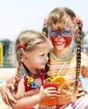Crianças com suco bebendo da pintura da face. Imagens de Stock