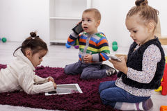 Crianças com tabuleta e telefones fotografia de stock royalty free