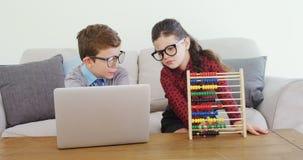 Crianças como o executivo empresarial que disusing sobre o portátil 4k video estoque