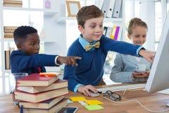 Crianças como os executivos empresariais que discutem sobre o computador de secretária fotos de stock