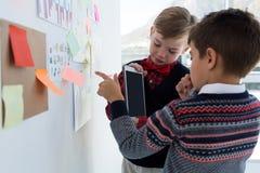 Crianças como os executivos empresariais que discutem sobre o whiteboard foto de stock