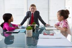 Crianças como os executivos empresariais que interagem ao encontrar-se imagem de stock royalty free