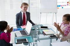 Crianças como os executivos empresariais que interagem ao encontrar-se imagens de stock