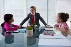 Crianças como os executivos empresariais que interagem ao encontrar-se foto de stock