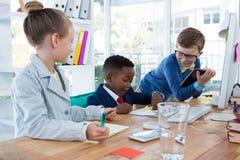 Crianças como os executivos empresariais que trabalham junto fotografia de stock royalty free