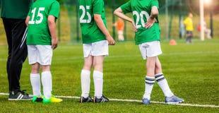 Crianças da equipe de futebol com o treinador no passo Jogadores de futebol novos Foto de Stock