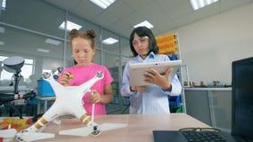 Crianças da escola em um laboratório Crianças que usam o equipamento especial para fixar um zangão video estoque