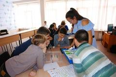 Crianças da escola na classe com mulher do professor Imagem de Stock Royalty Free