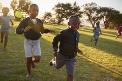 Crianças da escola primária que correm à câmera em um campo aberto Imagem de Stock