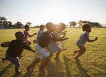 Crianças da escola primária que correm junto em um campo aberto Imagem de Stock Royalty Free