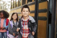 Crianças da escola primária que enfileiram-se para o ônibus escolar imagem de stock