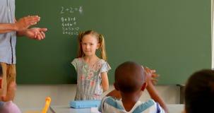 Crianças da escola que aplaudem a estudante na parte dianteira da classe na sala de aula na escola 4k filme