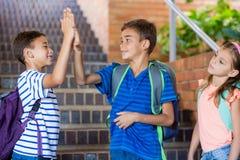 Crianças da escola que dão a elevação cinco na escadaria imagem de stock royalty free