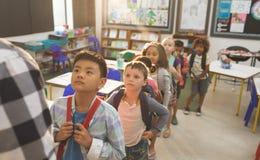 Crianças da escola que estão e que formam uma fila na sala de aula na escola fotos de stock