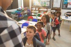 Crianças da escola que estão e que formam uma fila na sala de aula na escola fotografia de stock
