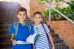 Crianças da escola que guardam um livro na escadaria fotos de stock royalty free