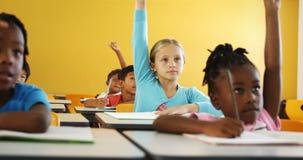 Crianças da escola que levantam a mão na sala de aula vídeos de arquivo
