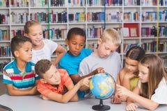 Crianças da escola que olham o globo na biblioteca fotografia de stock royalty free