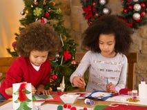 Crianças da raça misturada que fazem cartões de Natal Fotos de Stock Royalty Free