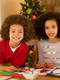 Crianças da raça misturada que fazem cartões de Natal Foto de Stock Royalty Free