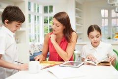 Crianças de ajuda da mãe com trabalhos de casa usando a tabuleta imagens de stock royalty free