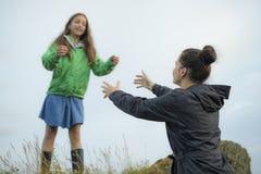 Crianças de ajuda da mãe a saltar fora das rochas imagem de stock royalty free