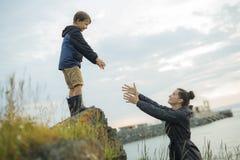 Crianças de ajuda da mãe a saltar fora das rochas imagens de stock royalty free