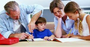 Crianças de ajuda do pai e da mãe com trabalhos de casa video estoque