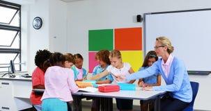 Crianças de ajuda do professor com seus trabalhos de casa na sala de aula vídeos de arquivo