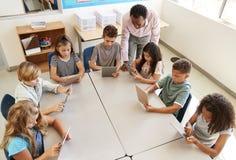 Crianças de ajuda do professor que usam tabuletas na lição, vista elevado fotos de stock royalty free